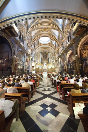 SANTA MARIA DE MONTSERRAT, SPAIN - 9 APRIL: Worshipers during worship in catholic church on April 9, Montserrat mountain, Spain. Santa Maria de Montserrat in  greatest monastery of Catalonia
