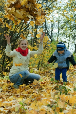throw up: Happy mother with   boy throw up maple leaves in autumn