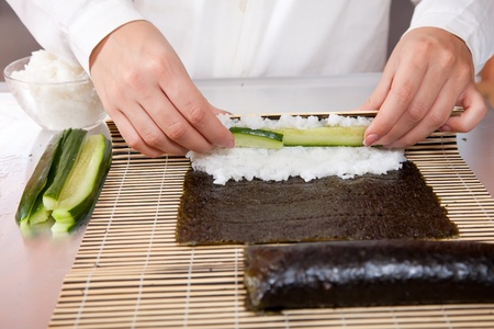 Closeup of cook making  Japanese sushi rolls  with cucumber photo