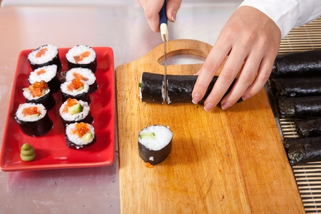 Gros plan de la fabrication de rouleaux cuisinier de sushis japonais
