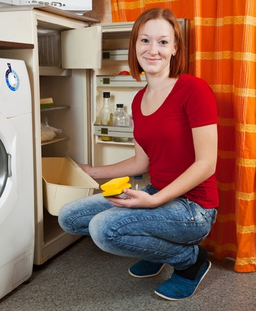 defrost: Young woman  defrosting the refrigerator at her kitchen