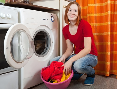 chore:  Young woman doing laundry at her home Stock Photo