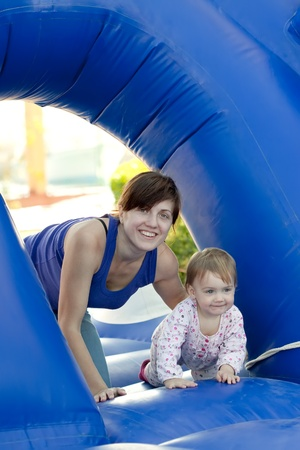 happy mother with  toddler on slide playground area photo