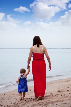 toddler walking: Rear view of  mother with  toddler walking  on sand beach
