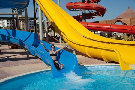 girl in swimming pool water slide at aquapark photo