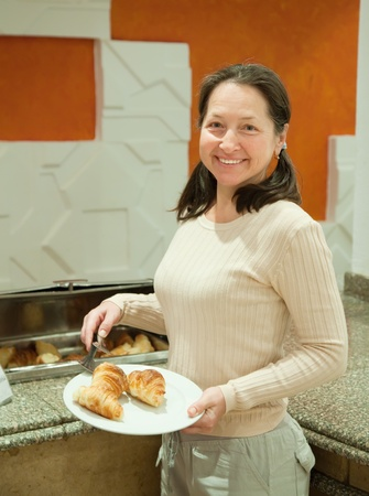 woman takes fresh croissant   in buffet at hotel photo