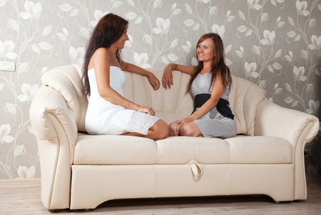 Two mid adult women talking on sofa in home photo