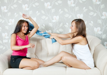 Happy women fighting with clothes on sofa in livingroom at home photo