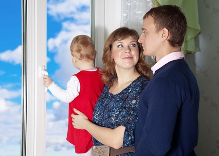 looking out: Parents with a child looking out the window in home Stock Photo