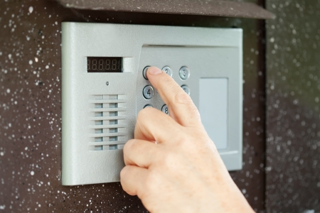Human finger pushing button of house intercom  photo