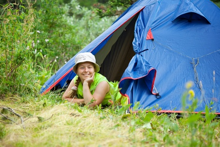woman lying in camp tent and looking at camera photo