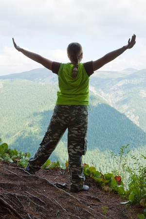 woman standing on  rock with raised hands  at mountain peak photo