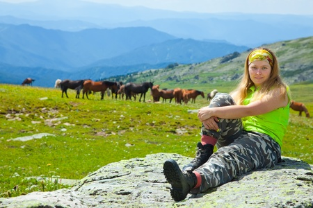 tourist sitting on stone against herd of horses at mountains  photo