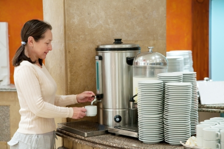 percolator: Woman pours  coffee from  coffee machine  Stock Photo