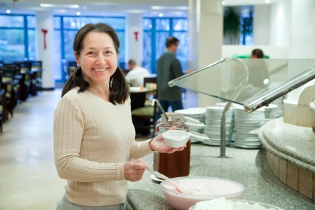 Woman takes dairy food on the buffet table photo