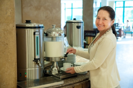 Woman pours milk to coffee at hotel restaurant photo