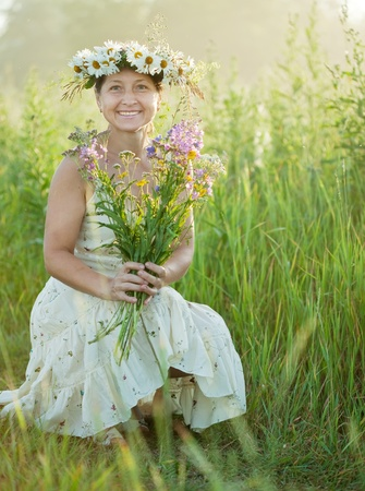 chaplet: Outdoor portrait of  happy mature  woman in  camomile chaplet Stock Photo