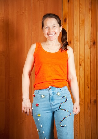 stitchcraft: Mature woman  shows a handmade jeans beaded by herself Stock Photo