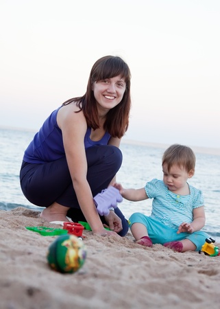 Happy mother with  toddler plays on sand beach Stock Photo - 12077306