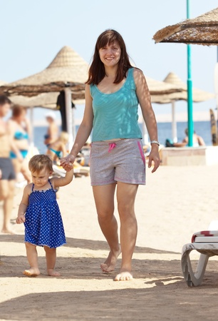 young mother with adorable toddler walking on beach photo
