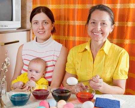Family coloring eggs for Easter holiday in kitchen Stock Photo - 12077281