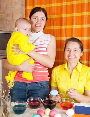 Family coloring eggs for Easter holiday in kitchen Stock Photo - 12077302