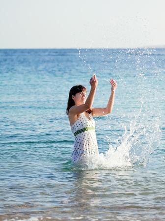 splutter: Happy  woman plays  on  sea  wave