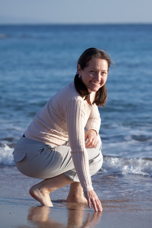Happy mature woman  on sandy beach photo