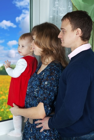 Parents with child looking out the window in home Stock Photo - 12238384