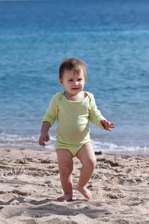 toddler walking: Happy toddler walking on sand beach