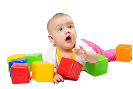 seven months baby girl plays with toy blocks over white background photo