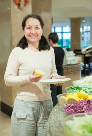 Woman takes fresh vegetables on table in buffet   photo