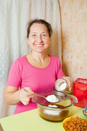 Mature woman making  dough in dish.One of the stages of cooking of  honey cake.  See series Stock Photo - 12288838