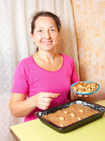 Mature woman adds nuts into dough.