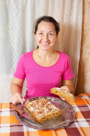 make a paste: Mature woman  with fresh  honey cake. One of the stages of cooking of  honey cake.  See series