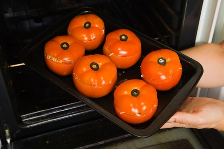 Closeup of cook hands putting stuffed tomato into oven.