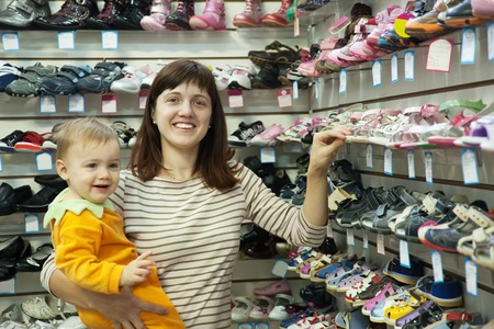 Happy mother with her child chooses baby shoes at fashionable shop