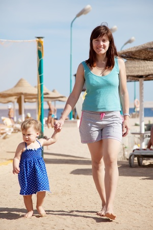 toddler walking:  full length shot of mother with  toddler walking  on sand beach Stock Photo