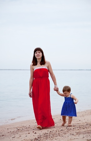 full length shot of mother with  toddler walking  on sand beach Stock Photo - 12288822