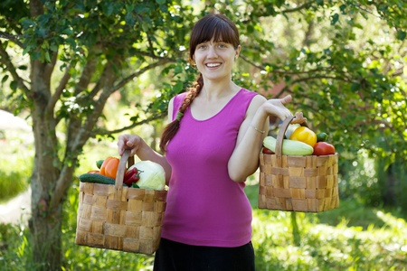 Happy girl with vegetables harvest in garden photo