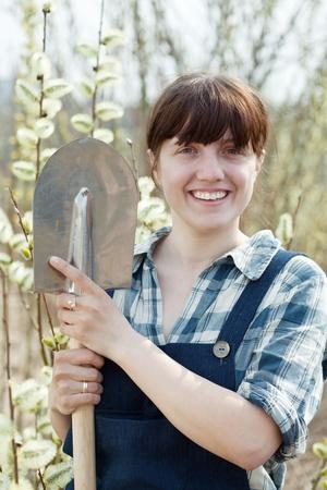Happy female farmer  with shovel in spring photo