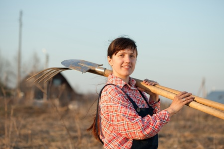 Happy female farmer  with spade and pitchfork in rural photo
