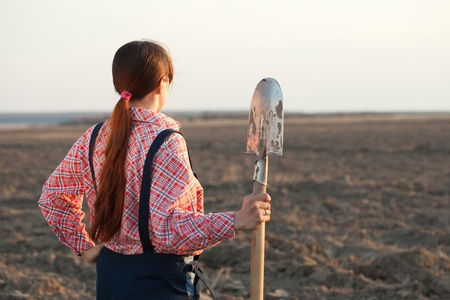 Female farmer  with spade in spring field photo