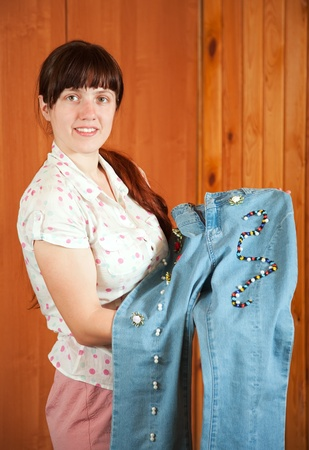 stitchwork: Woman shows a handmade jeans beaded by herself