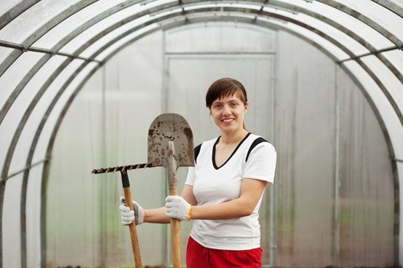 Happy female gardener with spade and rake in hothouse photo