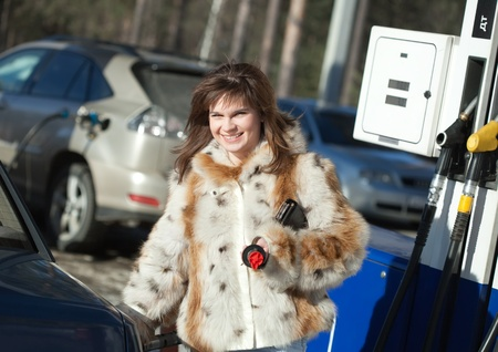 re fuel: Young  woman filling her car in winter Stock Photo
