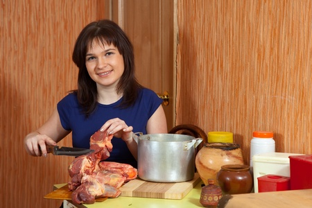 Young woman  cooking  beef in her kitchen photo
