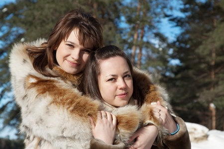 Outdoor winter portrait of happy women in wintry clothes photo