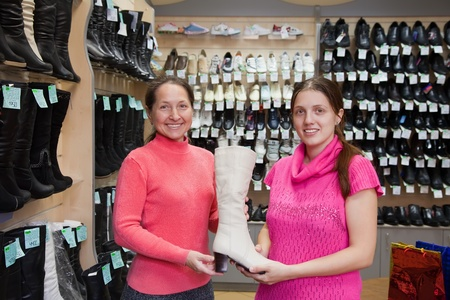 Two women chooses high boots at shoes shop
