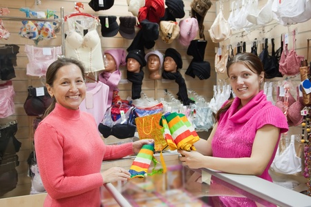 Saleswoman and customer with purchases at  counter in clothes shop